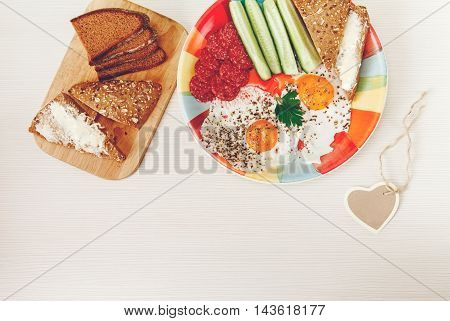 Delicious Tasty Breakfast from Eggs,Bread with Butter,Sausage on the Colorfull Plate.Wish Heart Card.White Background.Top View