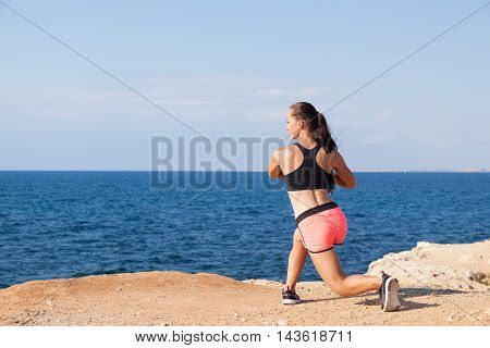 beautiful girl engaged in fitness on the beach by the sea