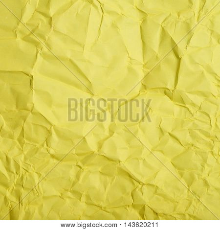 Close-up fragment of a yellow crumpled paper texture as a backdrop composition