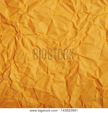 Close-up fragment of an orange crumpled paper texture as a backdrop composition