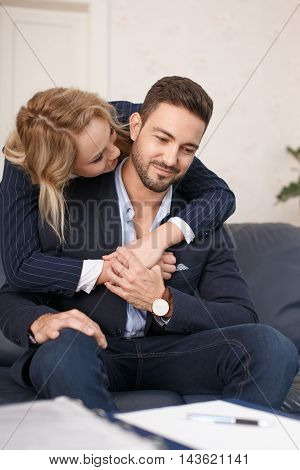 Blonde young businesswoman embrace businessman in office