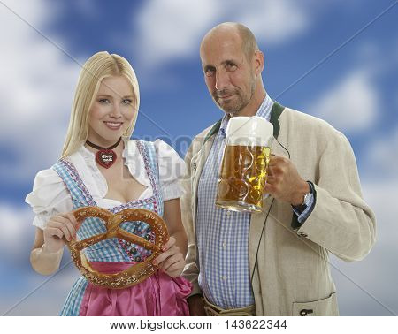 Bavarian Oktoberfest Couple with beer mug and pretzel with a blue cloudy sky in the background