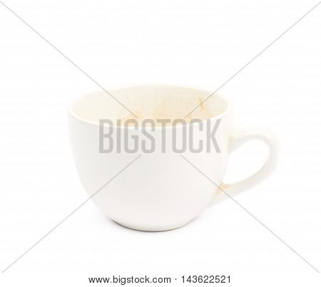 Dirty ceramic cup with a coffee leftovers isolated over the white background