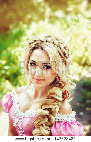Beautiful young woman with long hair braided in a braid, sitting in the woods.