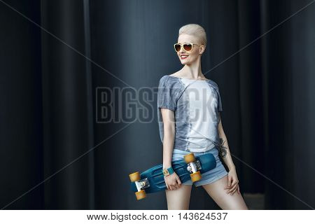 Fashion happy smiling hipster cool girl in sunglasses with skateboard behind the black urban background