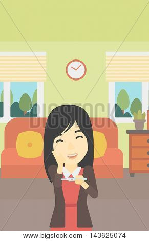 An asian delighted woman looking at positive pregnancy test on the background of living room. Young woman checking pregnancy test. Vector flat design illustration. Vertical layout.