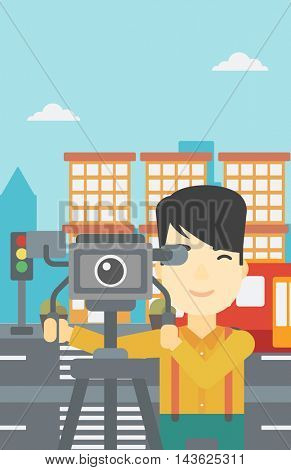An asian young cameraman looking through movie camera on a tripod. Young man with professional video camera in the city. Vector flat design illustration. Vertical layout.