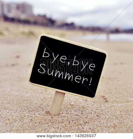 closeup of a black signboard with the text bye, bye summer written in it, on the sand of a beach