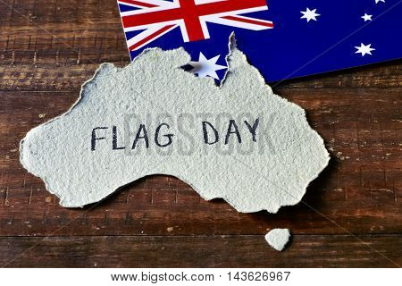closeup of an Australian flag and a piece of paper cut in the shape of Australia with the text flag day handwritten in it