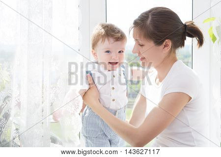 Young mother holding her newborn child. Mom nursing baby. Woman and new born boy relax in a white bedroom. Nursery interior. Mother breast feeding baby. Family at home