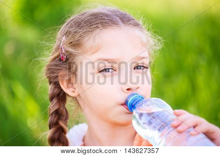 Little cute girl on the nature drinks water from a plastic bottle