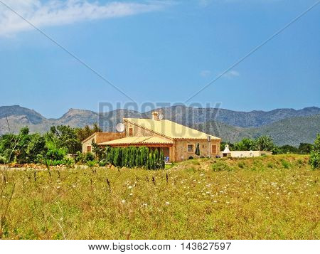 Pollenca Majorca Spain - June 28 2008: Finca vacation rental home with meadow on front surrounded by garden - tramuntana mountains in background