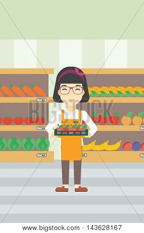 An asian young female supermarket worker holding a box with apples on the background of shelves with vegetables and fruits in supermarket. Vector flat design illustration. Vertical layout.