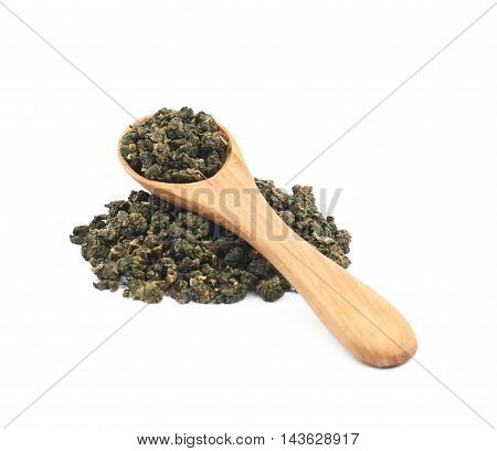 Pile of dried tea leaves with a wooden spoon over it, composition isolated over the white background