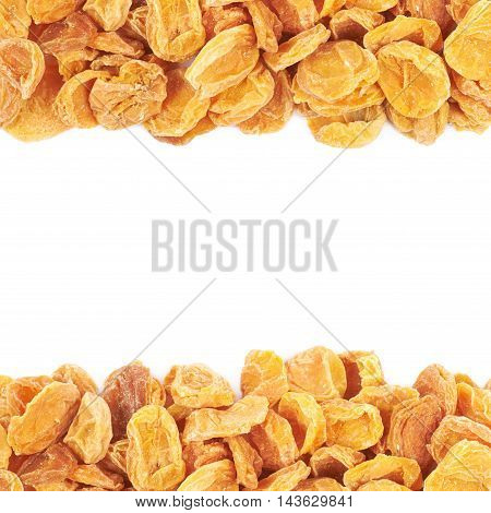 Copyspace backdrop composition with the borders made of dried apricot fruits isolated over the white background
