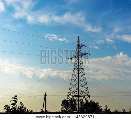 support high-voltage power lines against the blue sky.