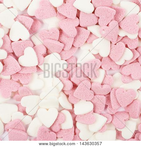 Surface coated with multiple pink sugar heart shaped sprinkles as a backdrop composition