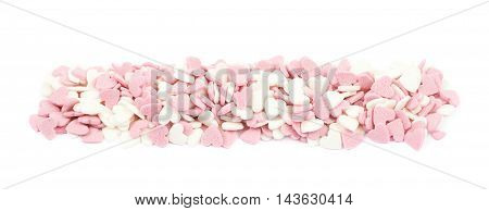 Line shaped pile of heart shaped sugar pink sprinkles isolated over the white background