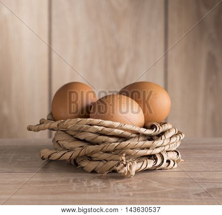 Chicken eggs in a nest of rope against the background of the fence in sunlight.