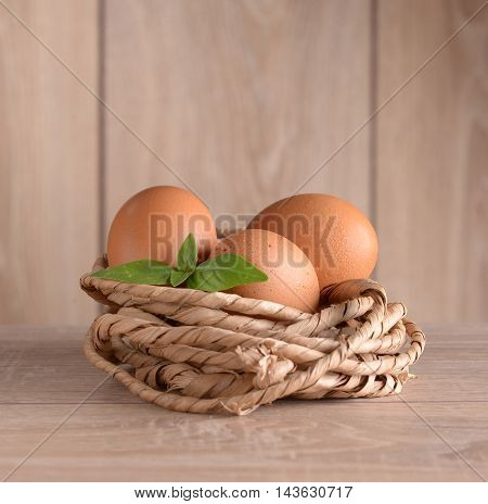 Chicken eggs in a nest of rope with basil leaves against the background of the fence in sunlight.