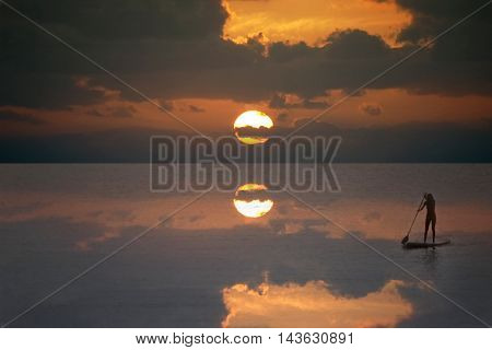 Silhouette of a stand-up paddle surfer (standup paddleboarding surfer) girl in the sea in a beautiful dawn