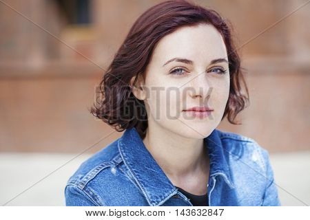 Closeup portrait of a happy young woman smiling, summer street outdoors