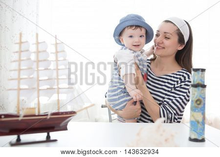 Travel Concept. Happy Sailor Kid And Mom Playing Indoors.