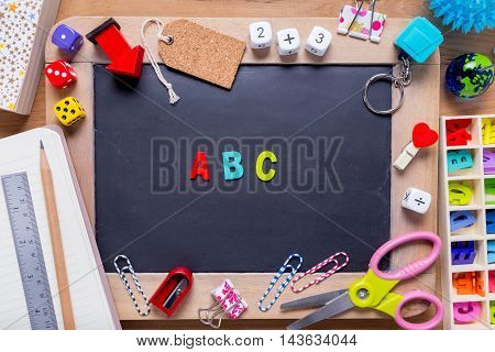 Small blackboard surrounded with various stationary with A B C alphabets in the middle on wood background