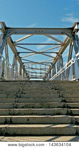 Photo of a pedestrian bridge over the railway. A pedestrian bridge. Stairs to the bridge. Metal bridge.