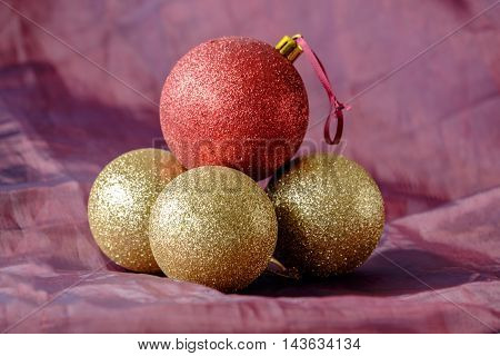 Group of bright shiny Christmas tree baubles on red cloth backdrop. Gold glitter baubles with one red balancing on top