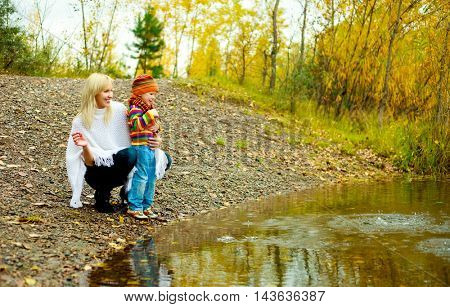 young mother and her son throwing stones to the lake outdoor in the autumn park