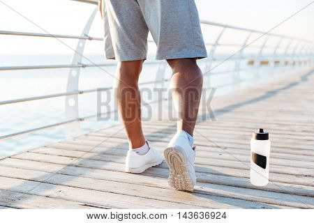 Cropped image of sports men legs doing exercises outdoors at the wooden pier