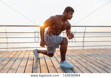 Concentrated african american young man athlete doing exercises on pier in the morning