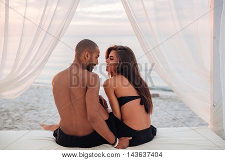 Back view of happy young couple sitting in bed on the beach