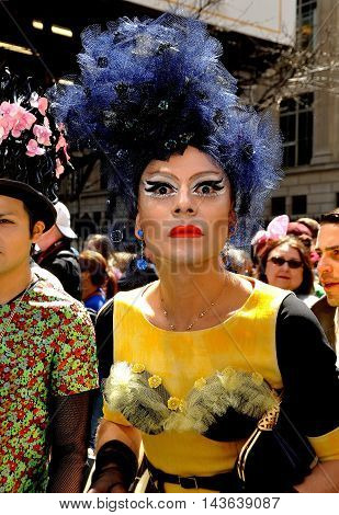 New York City - April 20 2014: Man in drag with a wild blue hat and heavy eye makeup at the Easter Parade on Fifth Avenue
