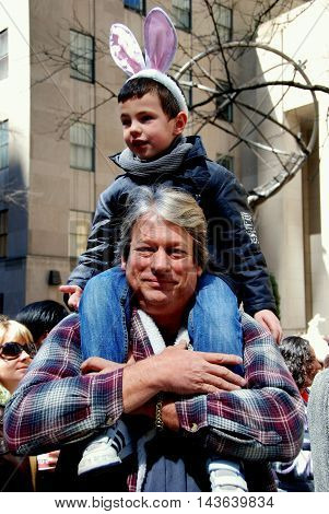 New York City - April 11 2009: Little boy wearing bunny ears sitting on his dad's shoulders for a better view of the Easter Parade on Fifth Avenue