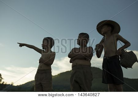 Silhouette of three boys The fishermen in the countryside