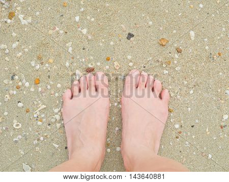 Woman standing barefoot on rough sand beach. Concept: Life is not always smooth sailing there will be tough times in life that you need to get through