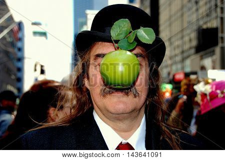 New York City - April 11 2009: Man in a bowler hat with an apple attached to his nose at the Easter Parade on Fifth Avenue