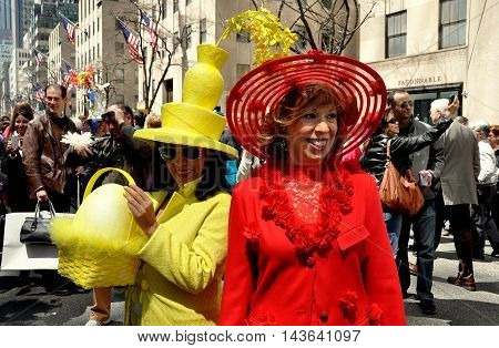 New York City - April 20 2014: Two women in chic yellow and red suits with creative bonnets at the Easter Parade on Fifth Avenue