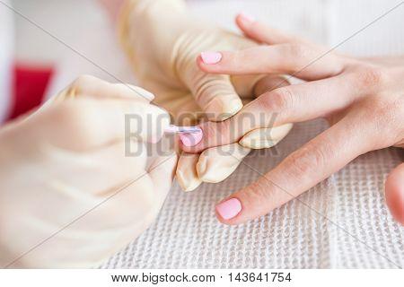 Manicure process in a beauty salon. Close up photo.