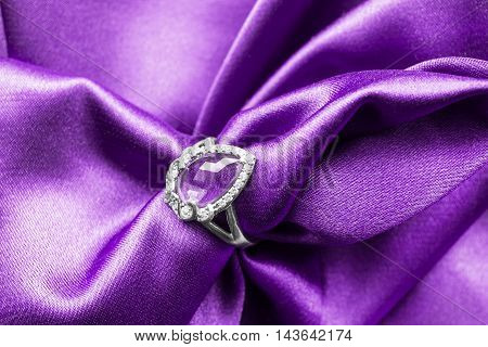 Silver amethyst ring on purple draped satin as a background