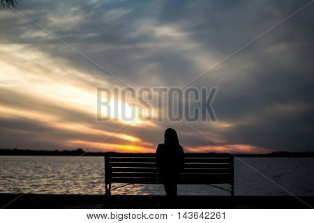 Lonely girl sitting on a bench and watching sunset near the sea