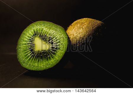 Fresh kiwi close up with drops of water on an old wooden table.