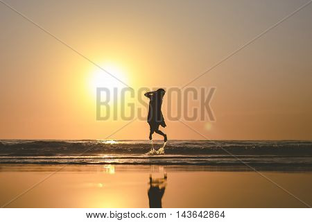 Silhouette of a woman bouncing up on the ocean beach during sunset