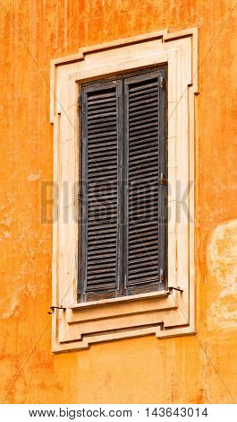 Old narrow window with wooden shutters closed on a bright yellow stucco wall