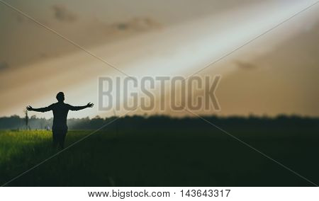 Man standing with arms outstretched in the Tribes on the background of the sun's rays