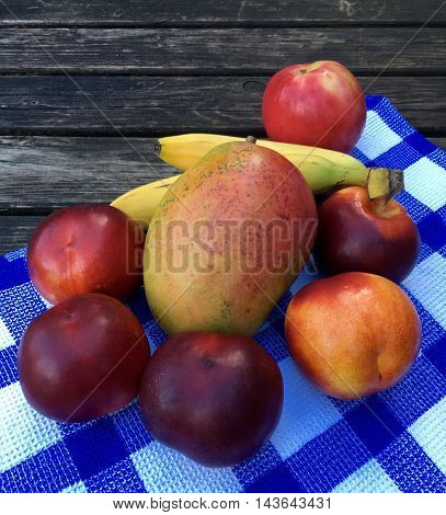 Fresh fruits with apples, nectarines and grapes on a dark table