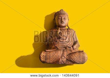A figure of Buddha over a Yellow Background