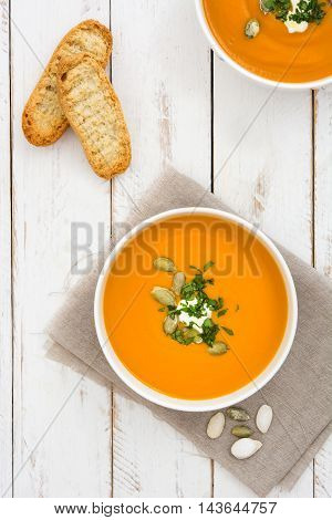 Pumpkin soup on a white wooden table